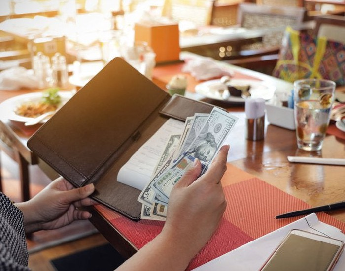 A woman placing cash in a check folder while sitting at a table in a restaurant.