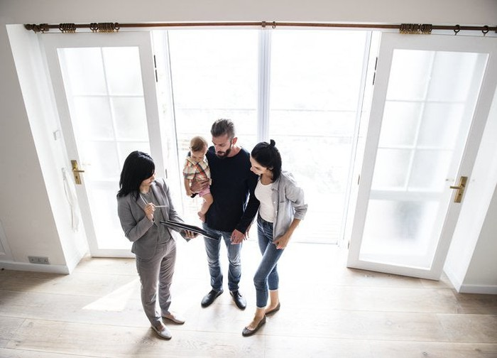 A real estate agent shows a couple with an infant a house.