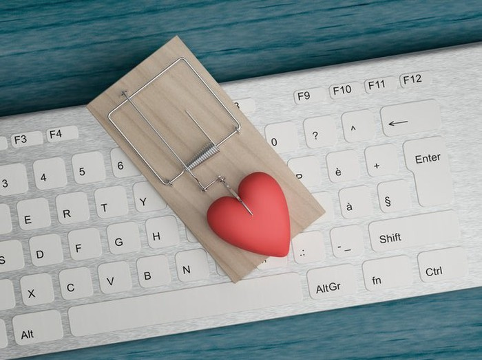 A mouse trap baited with a plastic heart sits on top of a keyboard.