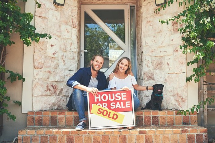 """A couple on a porch, holding a """"sold"""" sign."""