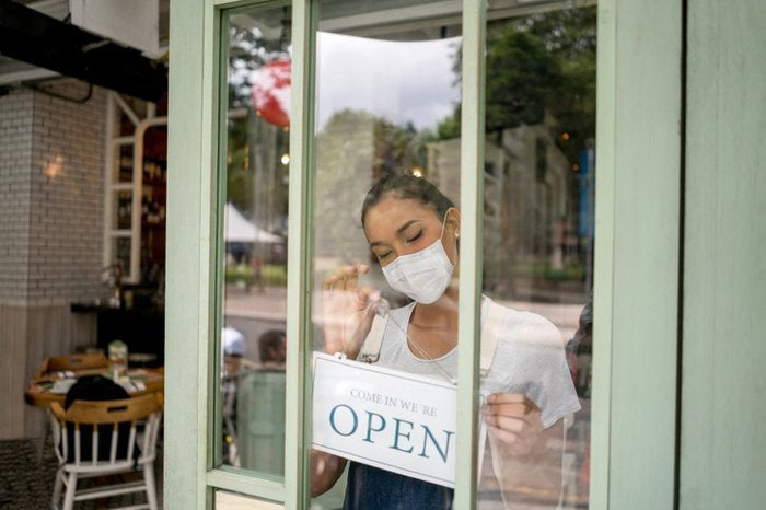 A small business owner wearing a mask and hanging an Open sign on the front door of her shop.