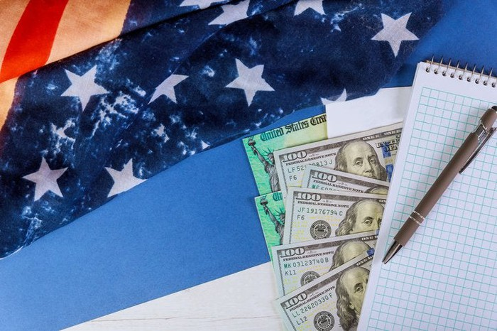 Money and a notepad atop an American flag.