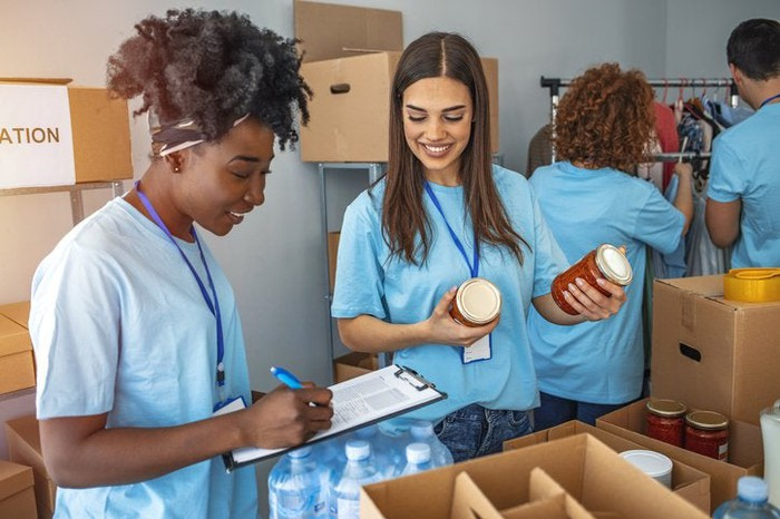 Two women organizing a food drive with boxes of canned food.