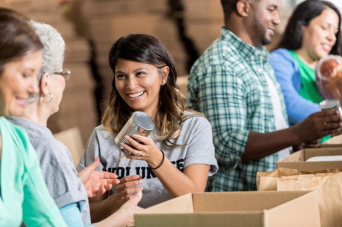 A group of smiling volunteers packing canned food in boxes.
