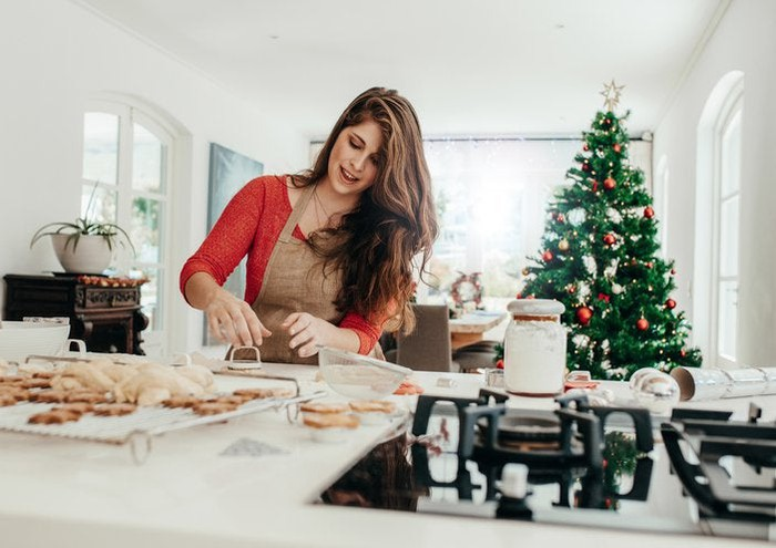 A woman baking cookies in her kitchen with a Christmas tree in the background.