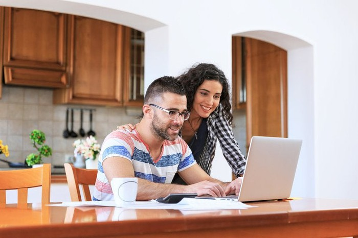 A young couple looking up information on a laptop while sitting in their kitchen.