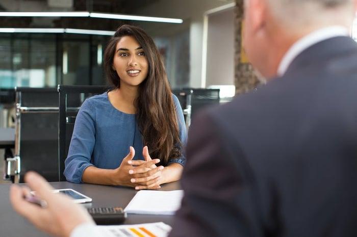 Une jeune femme assise en face d'un homme dans un bureau pour un entretien d'embauche.