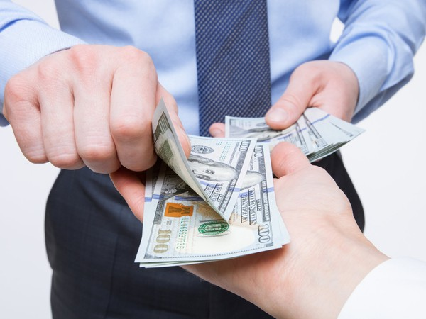 A hand passing cash into another person's hand.