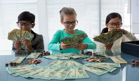 Three young kids with piles of money.
