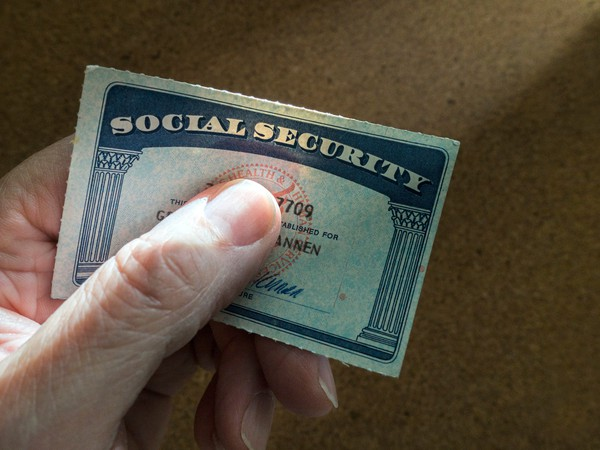 A person tightly grasping a social security card under their thumb.