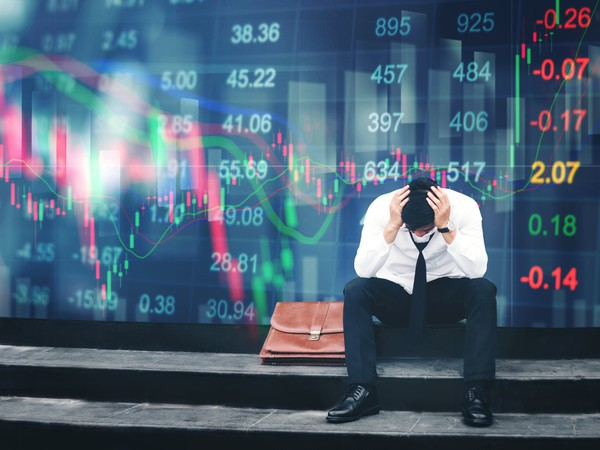 An upset businessman sits in front of a screen showing plunging stock prices.