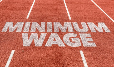 Minimum wage in white paint on a red track field.