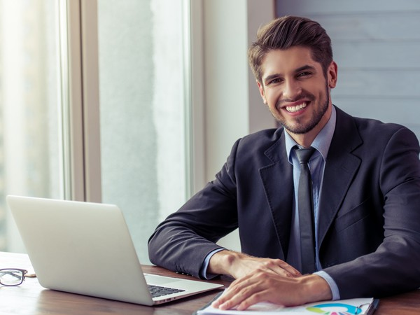 Smiling man in business suit at laptop.