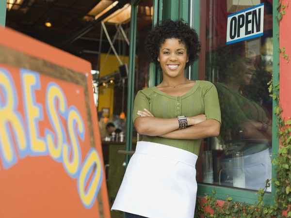 smiling woman wearing apron standing outside coffee shop with her arms folded -- entrepreneur small business POC