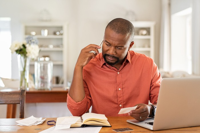 A man on the phone with his laptop and notebook open on the desk in front of him.