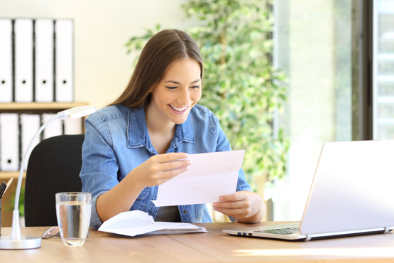 Woman reading a piece of paper at her desk